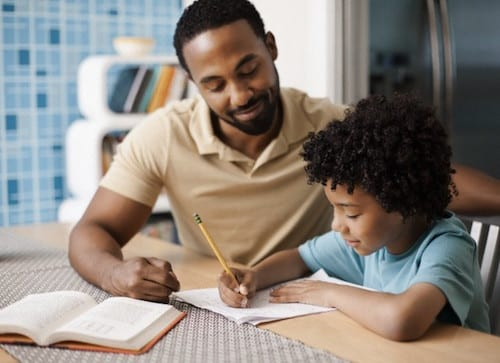 Father helping son (7-9) with homework