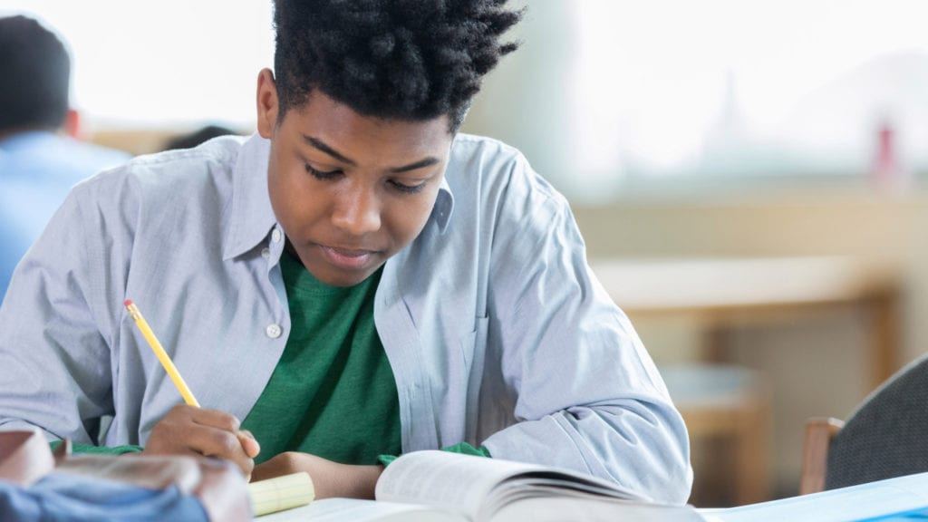 Teenage boy concentrates while studying in library